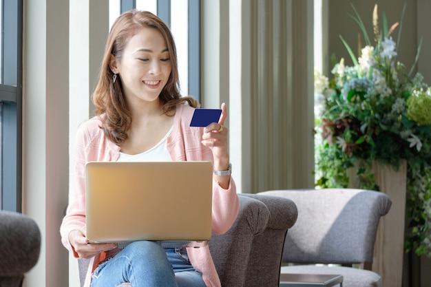 Mujer joven con tarjeta de crédito para compras en línea durante el uso de computadoras portátiles en estado de ánimo sonriente. Foto Premium