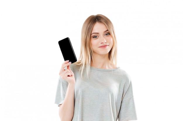 Mujer joven con teléfono móvil scren en blanco y mirando a cámara Foto gratis
