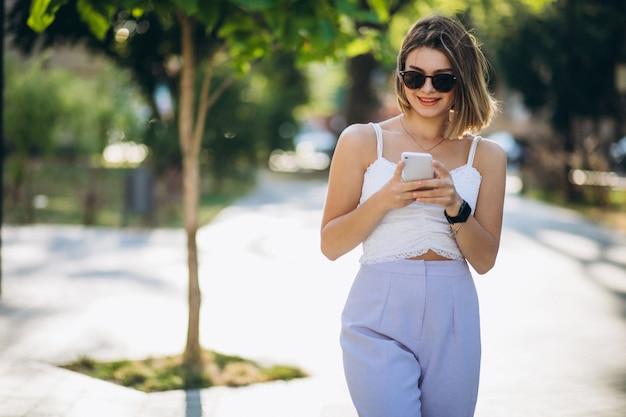 Mujer joven con teléfono en el parque Foto gratis