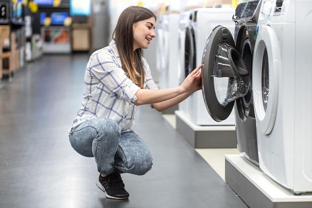 Una mujer joven en una tienda elige una lavadora. Foto gratis