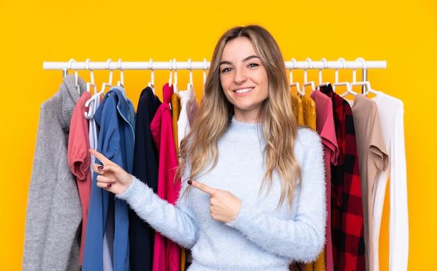 Mujer joven en una tienda de ropa apuntando con el dedo al lado Foto Premium