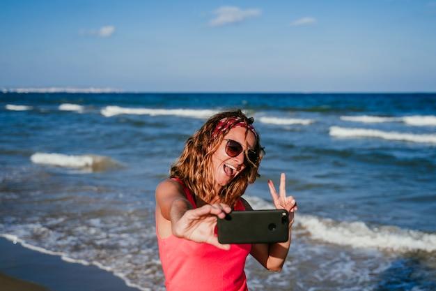 Mujer joven tomando una foto con un teléfono móvil en la playa. Foto Premium