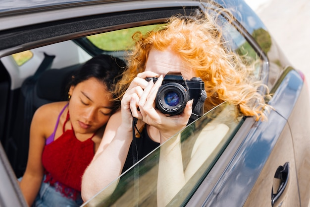 Mujer joven tomando fotos en la cámara Foto gratis