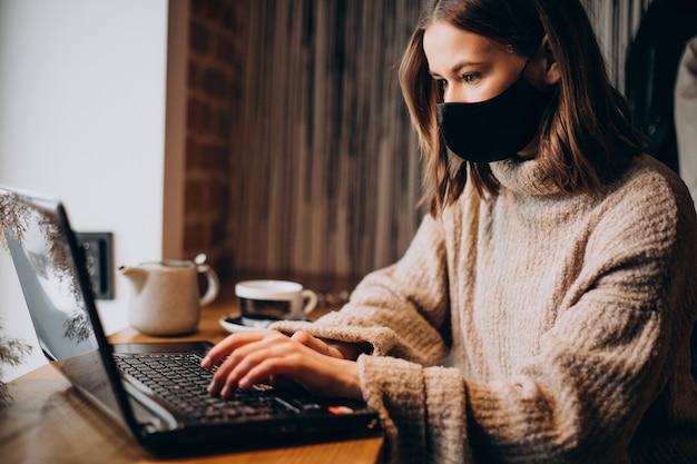 Mujer joven trabajando en un portátil en un café con máscara Foto gratis