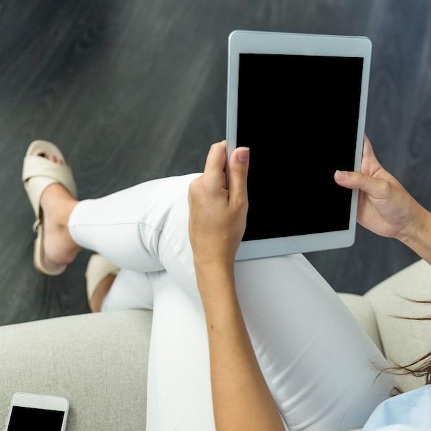 Mujer joven trabajando con tablet Foto gratis