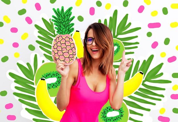 Mujer joven en traje de baño y gafas con piña Foto Premium
