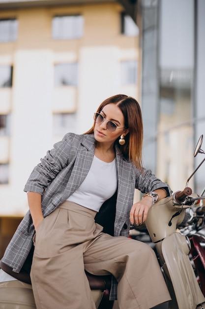 Mujer joven en traje de pie junto a la moto Foto gratis
