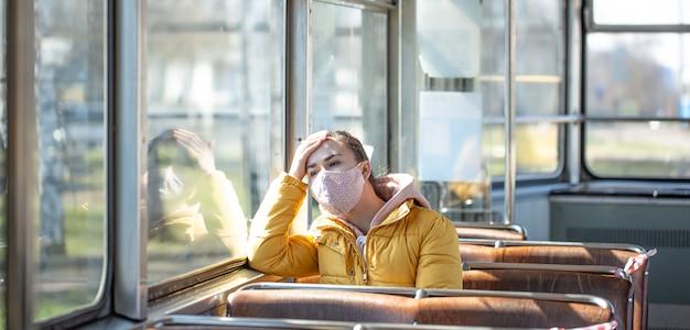 Una mujer joven en un transporte público vacío durante la pandemia. Foto gratis