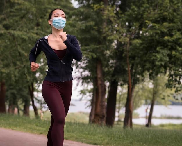 Mujer joven trotar con máscara médica en Foto Premium