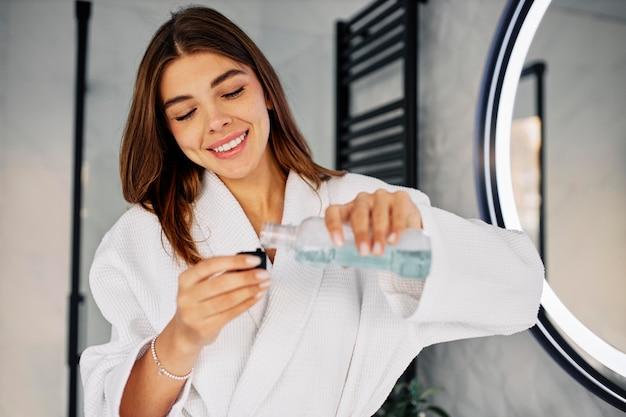 Mujer joven vertiendo enjuague bucal Foto gratis