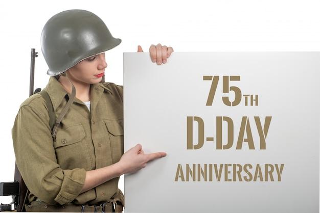 Mujer joven vestida con el uniforme militar de wwii con casco que muestra el letrero con el aniversario del día d Foto Premium