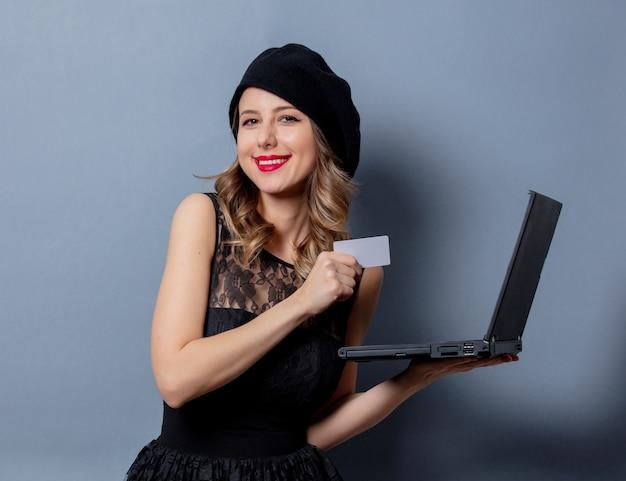 Mujer joven en vestido negro con cuaderno y tarjeta en la pared gris Foto Premium
