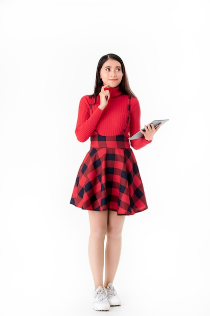 Mujer joven en vestido rojo lindo con la tableta. Foto Premium