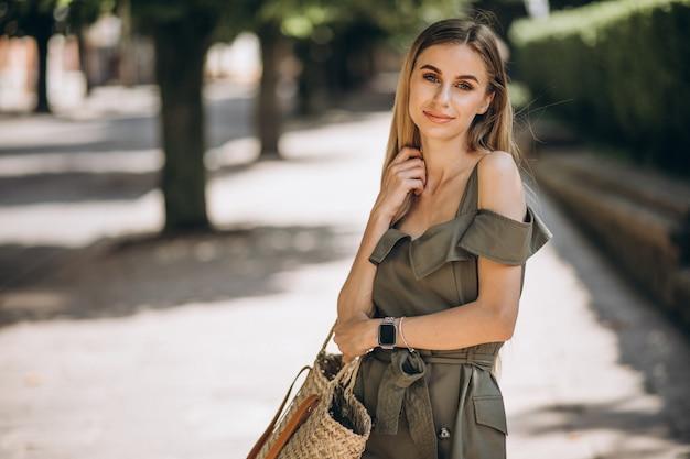 Mujer joven en vestido verde afuera en el parque Foto gratis