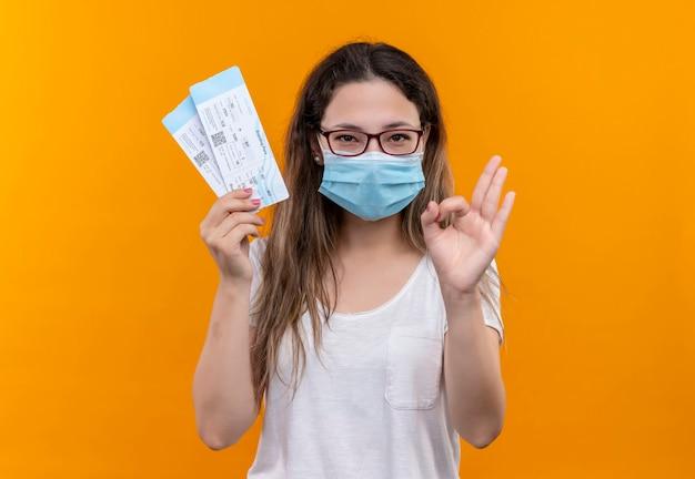 Mujer joven viajero en camiseta blanca con máscara facial protectora sosteniendo boletos de avión sonriendo haciendo bien firmar de pie sobre la pared naranja Foto gratis