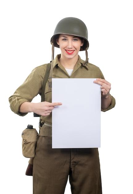 La mujer joven se vistió en los militares de wwii nosotros uniforme con el casco que muestra el letrero en blanco vacío con un copyspace Foto Premium