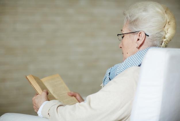 Mujer jubilada concentrada que lee el libro viejo Foto gratis