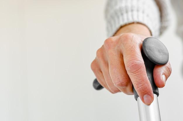 Mujer jubilada que sostiene el bastón del metal disponible. concepto médico y sanitario. copia espacio Foto Premium