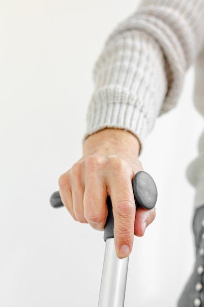 Mujer jubilada que sostiene el bastón del metal disponible. concepto médico y sanitario. Foto Premium