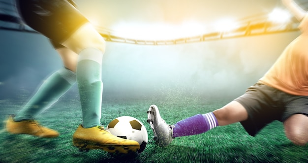 Mujer de jugador de fútbol en jersey naranja deslizamiento abordar el balón de su oponente Foto Premium