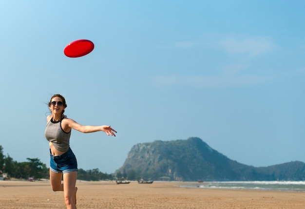Una mujer está jugando frisbee en la playa Foto Premium
