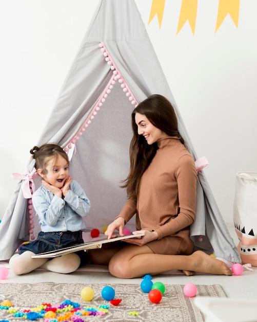 Mujer jugando con niña feliz en tienda Foto gratis