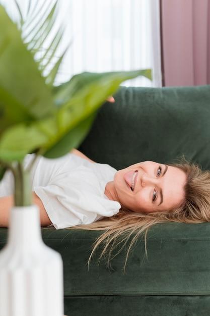 Mujer jugando y planta de primer plano Foto gratis