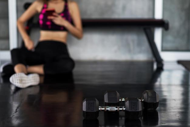 Mujer jugar teléfono inteligente después de entrenamiento con mancuernas Foto Premium