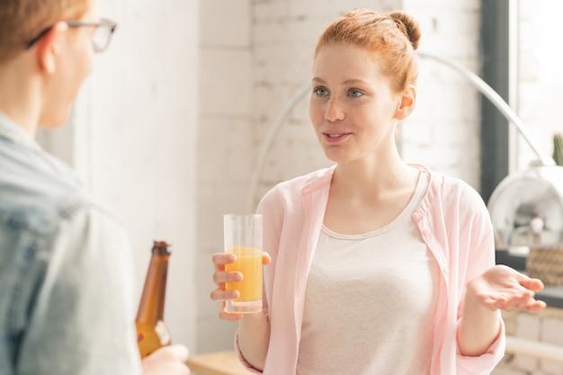 Mujer con jugo y hombre con cerveza hablando en fiesta Foto Premium