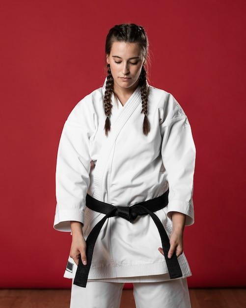 Mujer de karate de lado en kimono blanco tradicional sobre fondo rojo. Foto gratis
