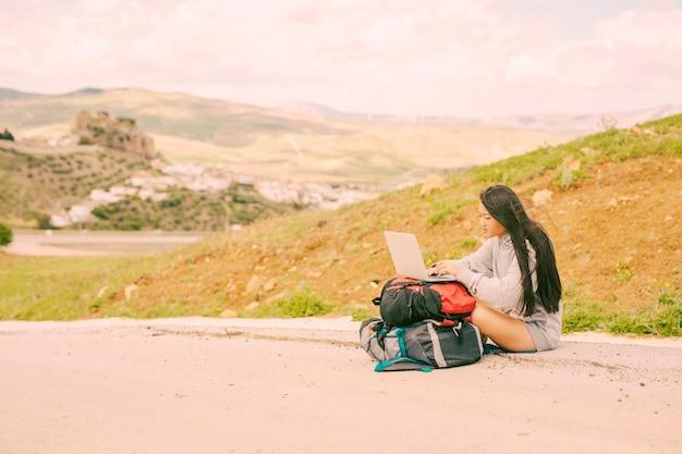 Mujer en el lado de la carretera y escribiendo en la computadora portátil en las mochilas Foto gratis