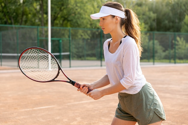 Mujer de lado jugando al tenis Foto gratis