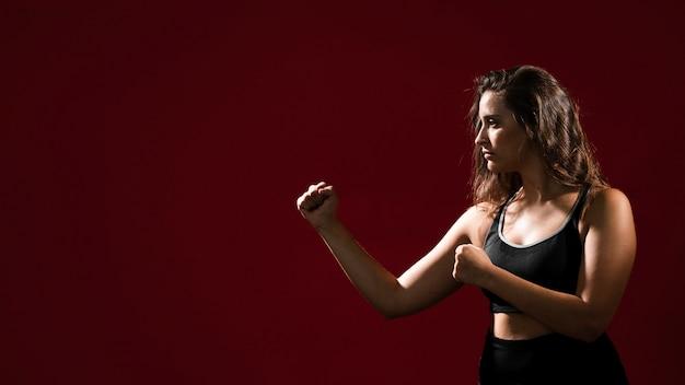Mujer de lado lista para dar un puñetazo y copiar espacio Foto gratis