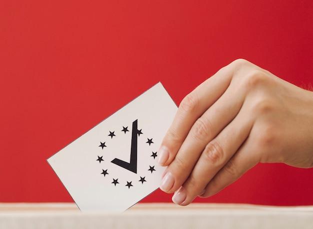 Mujer de lado poniendo una tarjeta de votación europea en una caja Foto gratis