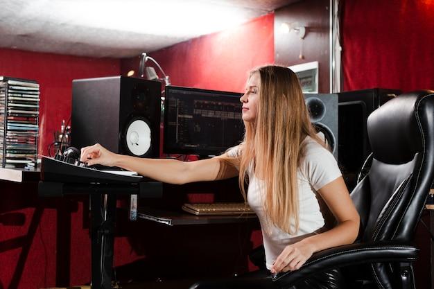 Mujer de lado sentado en un estudio y mirando auriculares Foto gratis