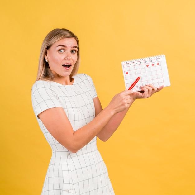 Mujer de lado en vestido blanco con calendario de período Foto gratis