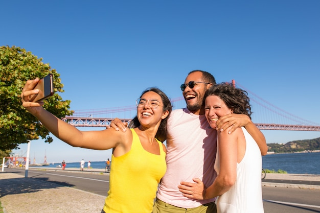 Mujer latina feliz tomando selfie grupal Foto gratis