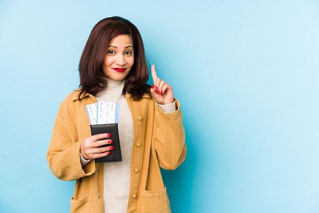 Mujer latina de mediana edad sosteniendo un pasaporte aislado mostrando el número uno con el dedo. Foto Premium