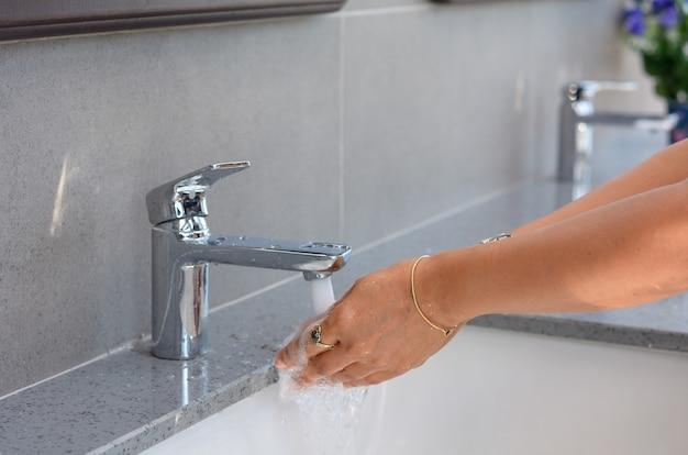 Mujer se lava las manos en el fregadero, limpieza de manos femeninas, lavado de manos Foto Premium