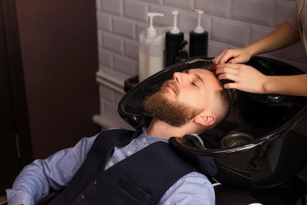Mujer lavando el cabello de un cliente en la peluquería Foto gratis