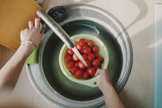 Mujer lavando tomates vegetales frescos Foto gratis