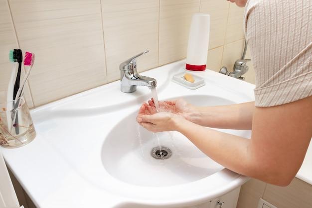 Lavabo Manos.Una Mujer Lavandose Las Manos Con Agua En El Lavabo Del Bano