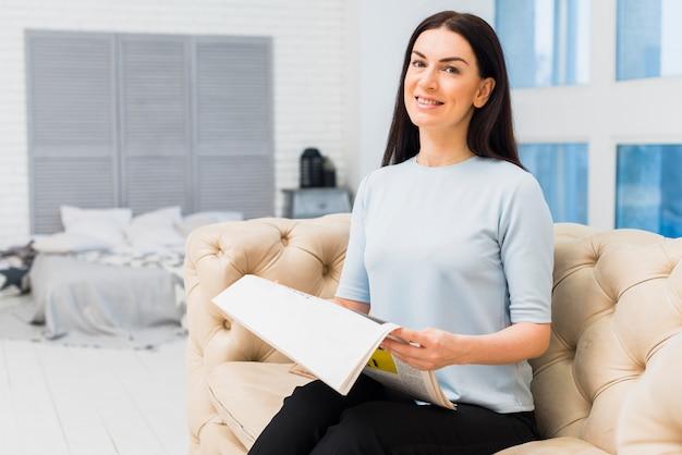 Mujer, leer el periódico, en, sofá Foto gratis