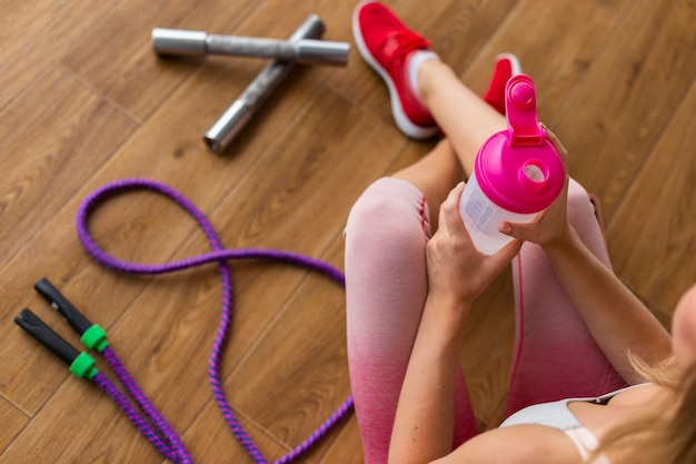 Mujer con leggins rosas y botella de agua Foto gratis