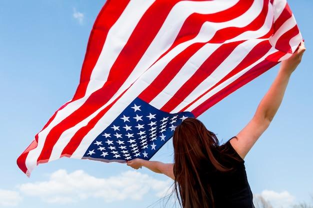 Mujer levantando la bandera estadounidense al cielo azul Foto gratis
