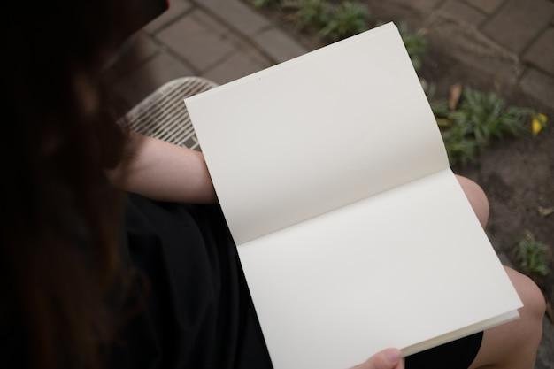 Mujer Leyendo El Libro En Blanco En El Jardín