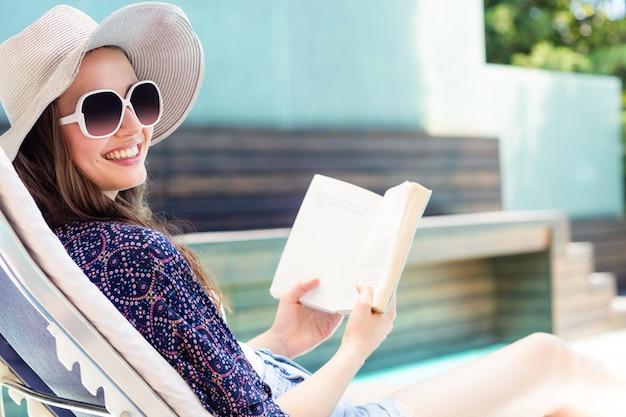 Mujer leyendo un libro junto a la piscina Foto Premium