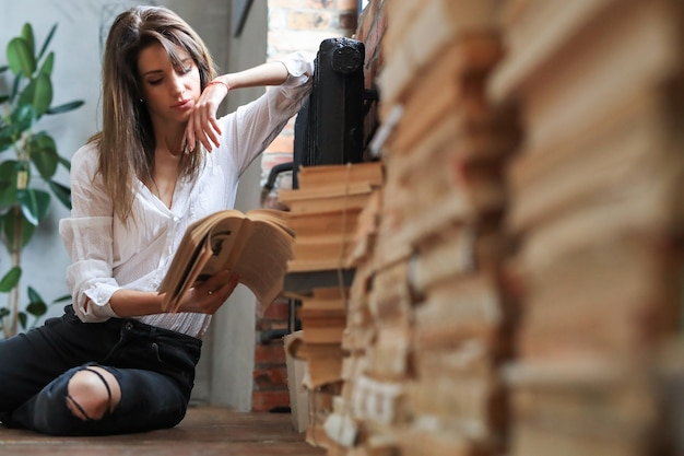 Mujer leyendo libros en el suelo Foto gratis