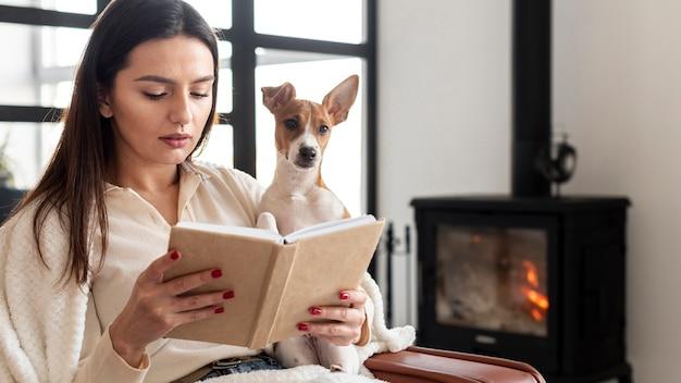 Mujer leyendo mientras sostiene a su perro Foto gratis