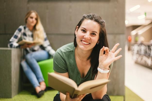 Mujer con libro haciendo gesto bien Foto gratis